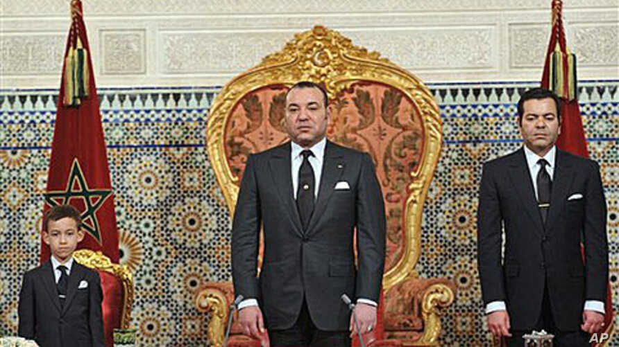 In this photo released by the Royal Palace, Morocco's King Mohamed VI flanked by his son Moulay El Hassan, left ,and his Brother Prince Moulay Rachid, right , listens to the national anthem after he delivered a speech to the nation, March, 9, 2011, a