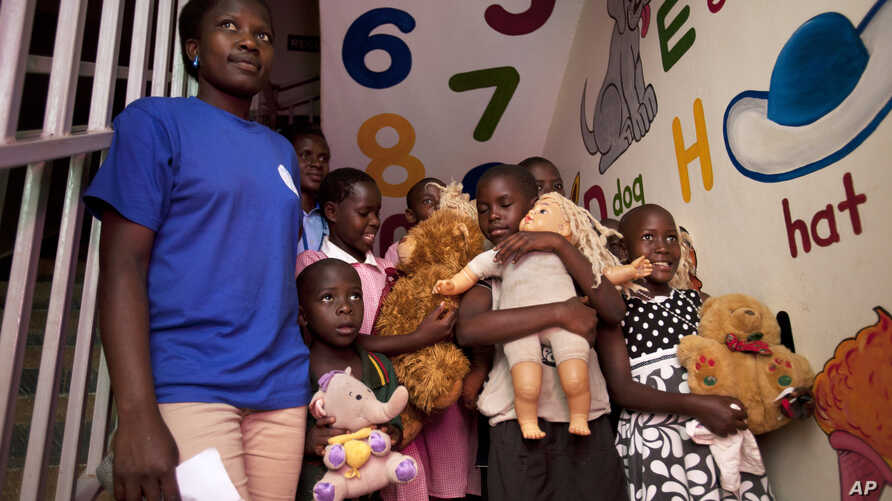 FILE - Ugandan children, orphans among them, are seen at a clinic in Kampala, Uganda, in a Aug. 3, 2012, photo.