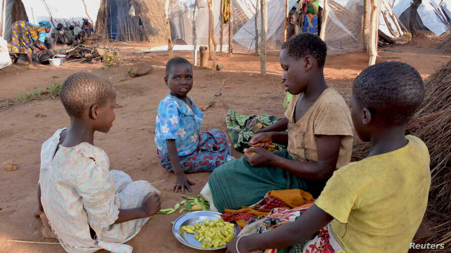 FILE - Mozambican child refugees prepare food at Kapise camp in Malawi's Mwanza district, Jan. 18, 2016.