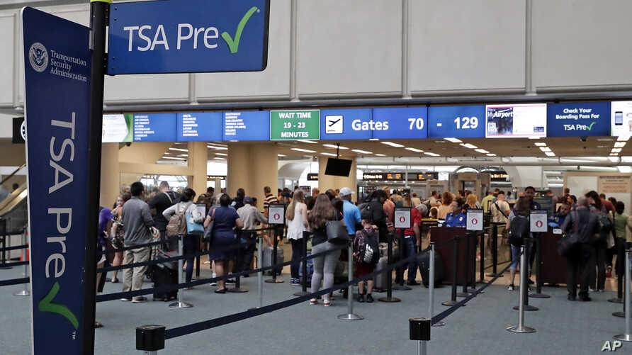 Air passengers heading to their departure gates enter TSA precheck before going through security screening at Orlando International Airport, June 21, 2018, in Orlando, Fla. The TSA is considering dropping security screening at smaller airports to con