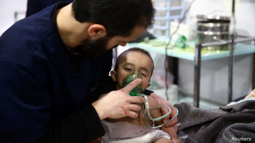 A man with a child at a hospital in the besieged town of Douma, Eastern Ghouta, Damascus, Syria February 25, 2018.