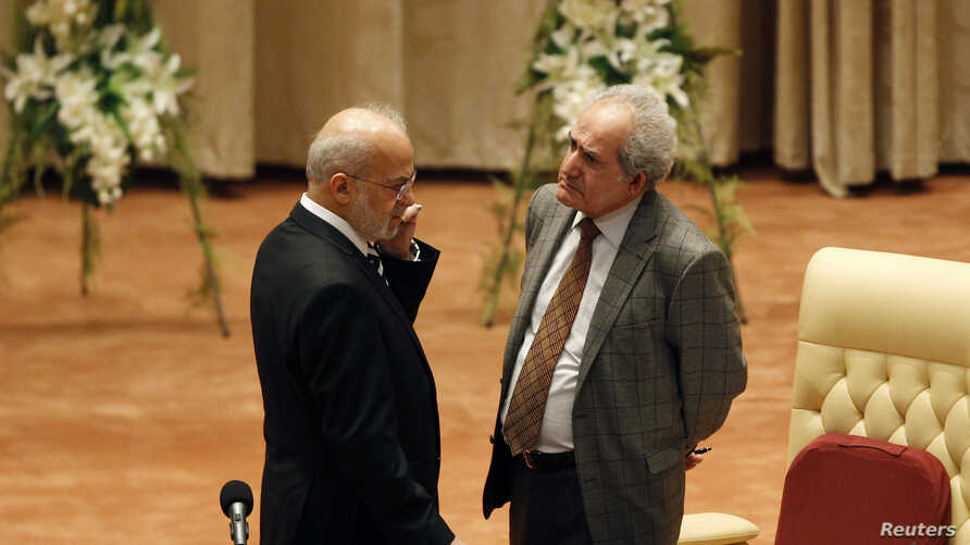 Mehdi al-Hafidh, right, theacting speaker of Iraq's newly elected parliament, talks to Iraq's former Prime Minister Ibrahim Jafari at the first session of the Iraqi parliament in Baghdad July 1, 2014.