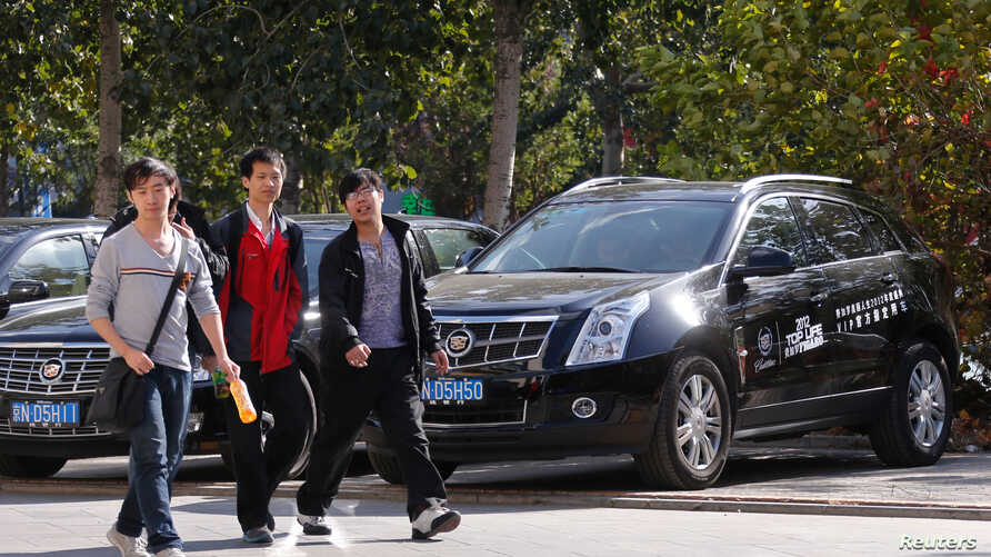 People walk past Cadillac cars outside a dealership in Beijing, October 31, 2012. General Motors plans to start manufacturing some of the luxury cars in China. announced