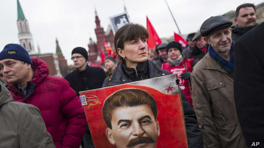 FILE - Communist party supporters hold portraits of Stalin as they line up to place flowers on his grave in Red Square, outside the Kremlin wall, to mark the 64th anniversary of his death in Moscow, Russia, March 5, 2017.