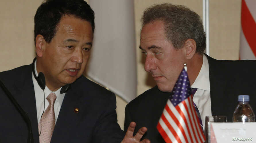 FILE - U.S. Trade Representative Michael Froman (R) speaks with Japan's Economics Minister Akira Amari as they take their seats before a news conference with other pacific rim ministers to conclude the Trans-Pacific Partnership (TPP) Ministerial meet