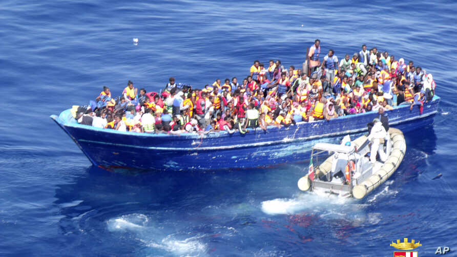 In this photo provided by the Italian Navy, migrants are approached by an Italian Navy dinghy boat in the Mediterranean sea, Aug. 22, 2015.