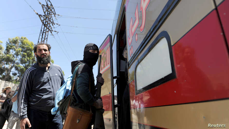 A masked rebel fighter boards a bus with his weapon as rebel fighters and their families evacuate the besieged Waer district in the central Syrian city of Homs, May 21, 2017.