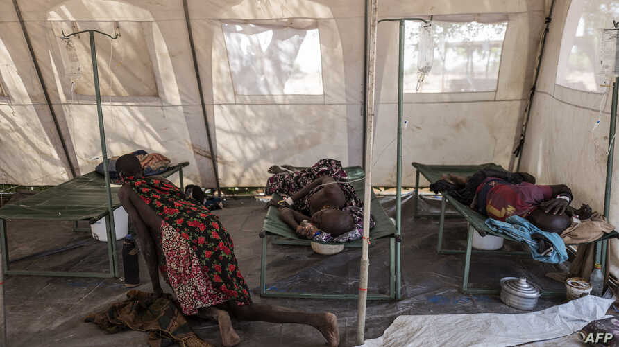 Patients suffering from cholera receive treatment inside a tent converted into a temporary field hospital near the remote village of Dor in the Awerial county in south-central Sudan, April 28, 2017.