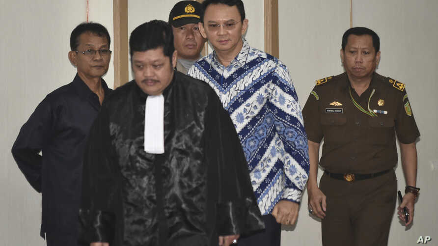 """Jakarta Governor Basuki """"Ahok"""" Tjahaja Purnama, center, is escorted by prosecutors as enters the court room for his sentencing hearing in Jakarta, Indonesia, May 9, 2017."""