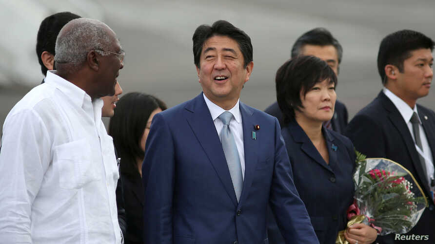 Japan's Prime Minister Shinzo Abe, center, talks to Salvador Antonio Valdes Mesa, a member of the Political Bureau of the Central Committee of the Communist Party of Cuba and vice president of the Council of State of Cuba, upon his arrival at Jose Ma