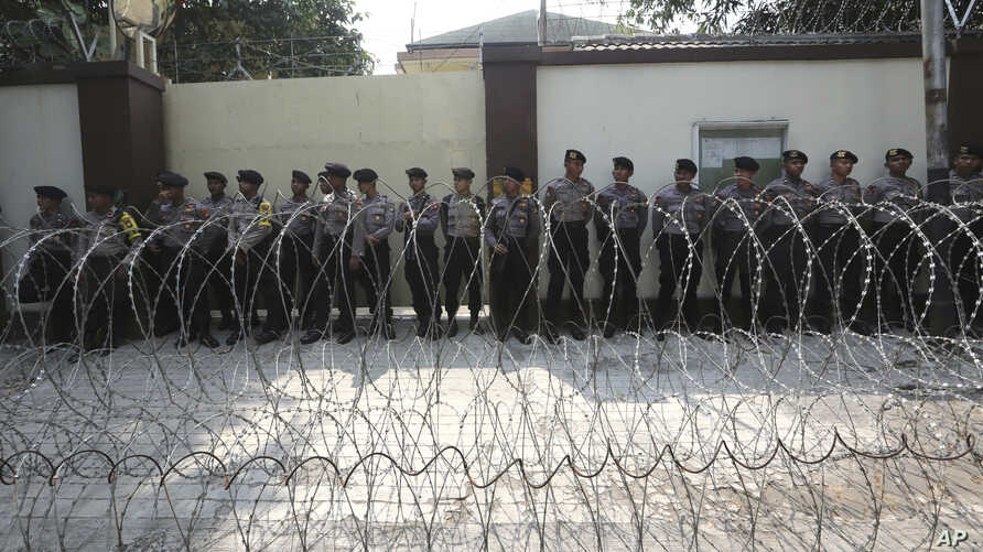 Police officers stand guard behind a razor wire barricade during a rally against persecution of Myanmar's Rohingya Muslim minority, outside Myanmar Embassy in Jakarta, Indonesia, Sept. 4, 2017.