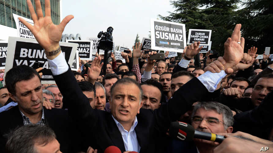 Ekrem Dumanli, editor-in-chief of Zaman newspaper, salutes cheering supporters as he is detained outside his office in Istanbul, Turkey, Dec. 14, 2014.