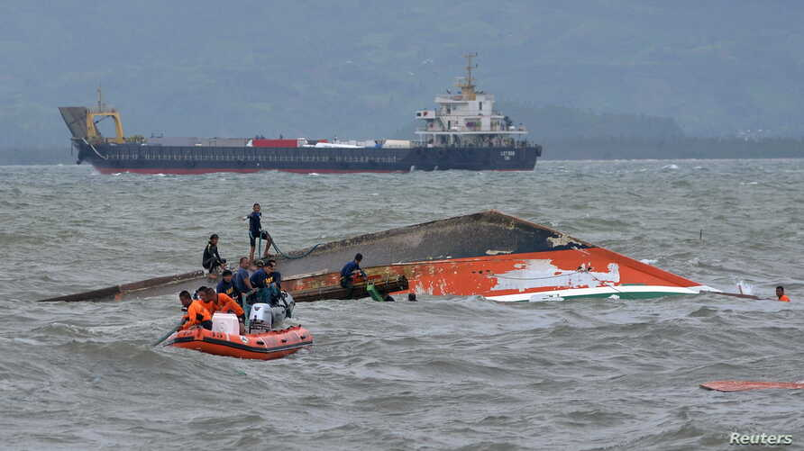 Rescuers tie a rope at the capsized vessel MBCA Kim-Nirvana to pull it towards the shore near a port in Ormoc city, central Philippines, July 3, 2015.