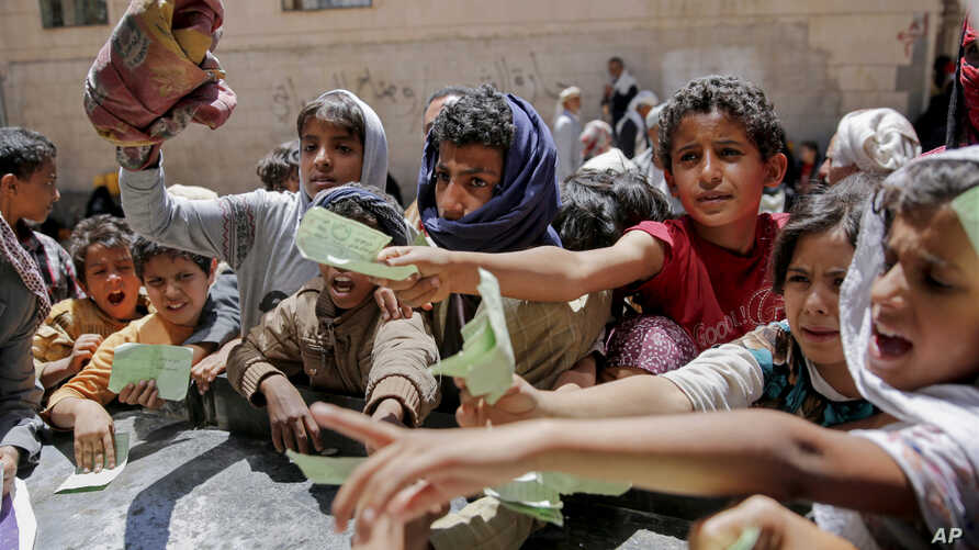 Yemenis present documents in order to receive food rations provided by a local charity, in Sanaa, Yemen, April, 13, 2017.