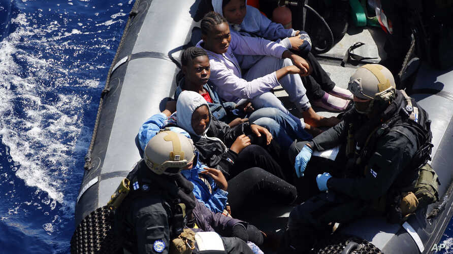 FILE - Rescued migrants sit in a German Navy boat besides Finish Special Forces,  prior to board the German combat supply ship 'Frankfurt am Main' during EUNAVFOR MED Operation Sophia in the Mediterranean Sea off the coast of Libya, March 29, 2016.