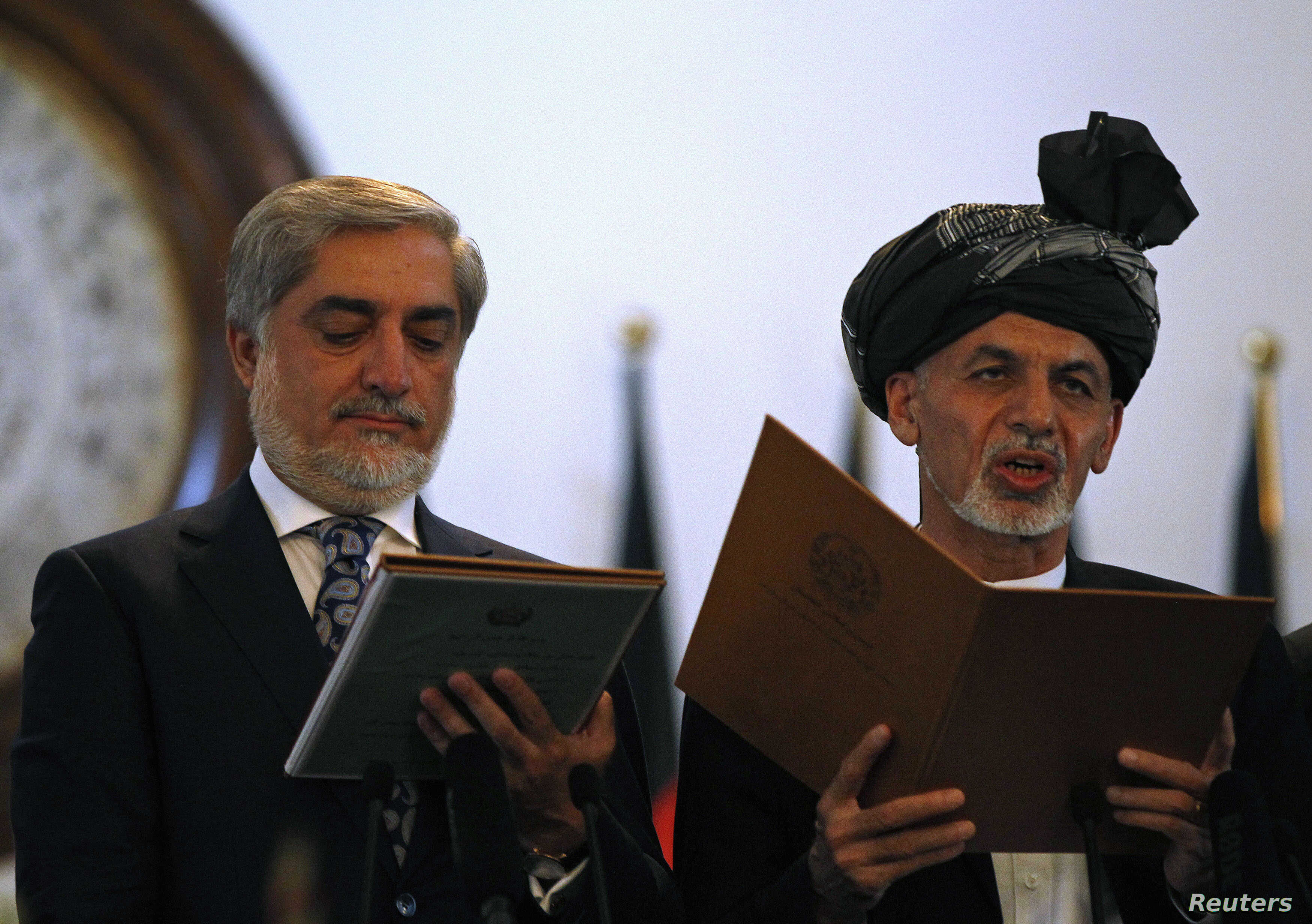 Afghanistan's new President Ashraf Ghani, right, and Afghanistan's Chief Executive Abdullah Abdullah take the oath during their inauguration in Kabul, Sept. 29, 2014.