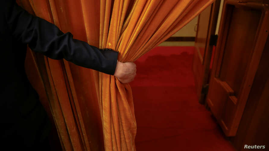 FILE - A security agent opens a curtain covering the entrance of a main hall inside the Great Hall of the People where sessions of the National People's Congress and the Chinese People's Political Consultative Conference take place, in Beijing, China