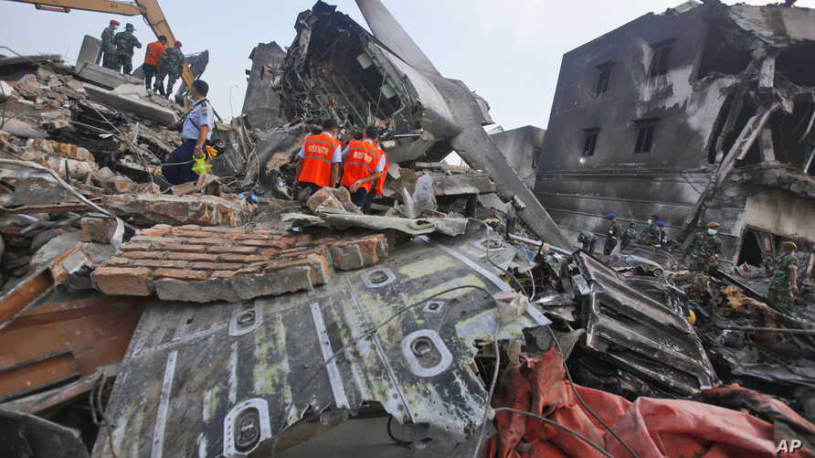 Investigators inspect the wreckage of the crashed air force transport plane in Medan, North Sumatra, Indonesia, Wednesday, July 1, 2015.