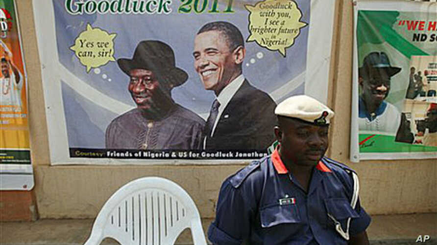 A Nigerian security man sits under a campaign poster of Nigeria President Goodluck Jonathan, with US President Barrack Obama, in Abuja, Nigeria, January 12, 2011