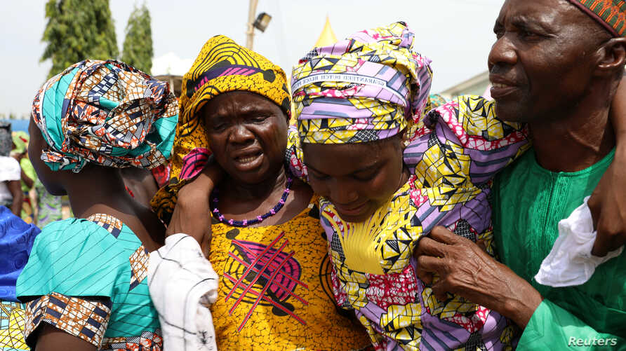 FILE - One of the newly released 82 Chibok school girls embraces her parents as she reunites with her family in Abuja, Nigeria, May 20, 2017.