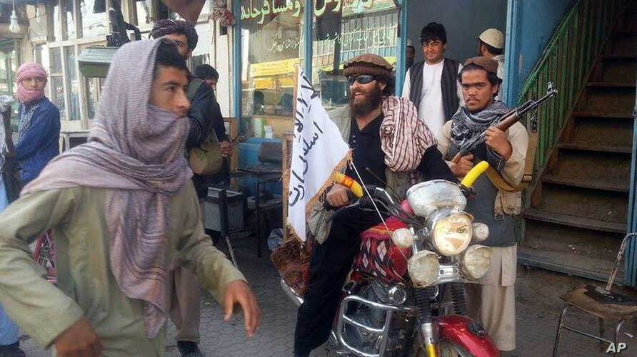 FILE - A Taliban fighter sits on his motorcycle adorned with a Taliban flag in a street in Kunduz, Afghanistan. Afghanistan's Taliban closed ranks around a new leader after months of infighting following the death of Mullah Mohammad Omar,  Sept. 29,