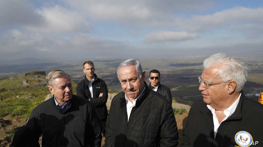 Israeli Prime Minister Benjamin Netanyahu, center, Republican U.S. Sen. Lindsey Graham, left, and U.S. Ambassador to Israel David Friedman, right, visit the border between Israel and Syria at the Israeli-held Golan Heights, March 11, 2019.