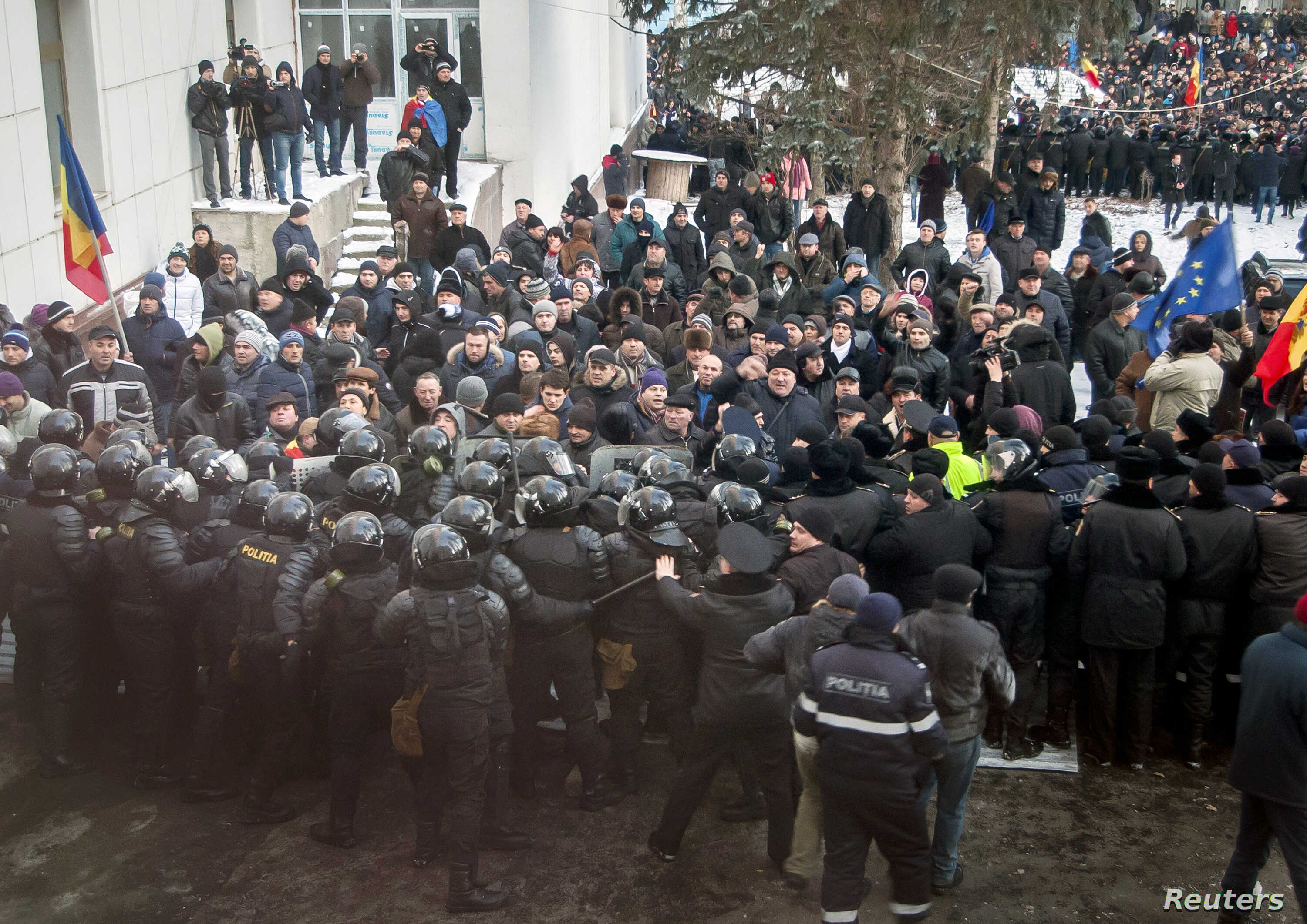 Protesters push a riot police line outside the parliament building in Chisinau, Moldova, Jan. 20, 2016. Hundreds of protesters broke through police lines on Wednesday to get into Moldova's parliament after it voted in a new prime minister.