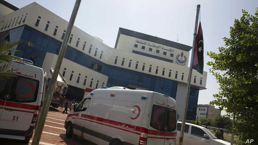 Ambulances and firefighters gather at the headquarters of the national oil company after an attack by gunmen in Tripoli, Libya, Monday, Sept. 10, 2018.
