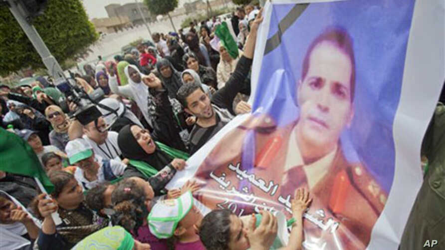 In this photo made on a government organized tour, supporters carry a poster of Libyab army colonel who was killed in NATO attack in April, during funeral ceremony for members Gadhafi family in Tripoli, Libya, May 2, 2011.