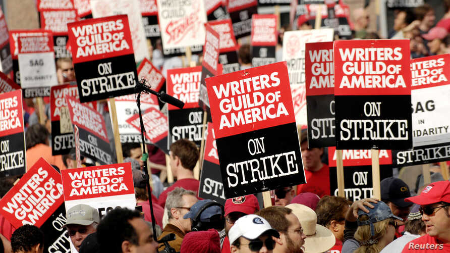 FILE - Thousands of Writers Guild of America members and supporters hold signs during a large strike outside the Fox studio lot along the Avenue of the Stars in Los Angeles, California, November 9, 2007.