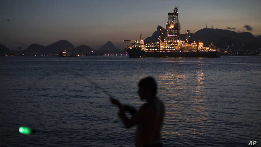FILE - In this March 28, 2018 photo, a man holds his fishing rod, carrying an illuminated bobber, on the shore of Guanabara Bay where Petrobras operates its ultra-deep drilling vessel Laguna Star NS-44, in Niteroi, Brazil.