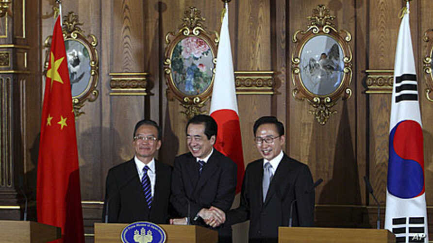 Chinese Premier Wen Jiabao, Japanese Prime Minister Naoto Kan and South Korean President Lee Myung-bak, left to right, shake hands at their joint news conference in Tokyo, May 22, 2011