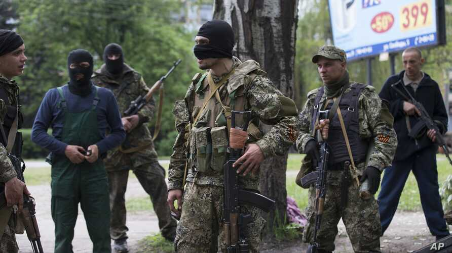 Pro-Russian gunmen listen to instructions from their commander, center, behind barricades in Slovyansk, eastern Ukraine, Friday, May 2, 2014. Ukraine launched what appeared to be its first major assault against pro-Russian forces who have seized gove