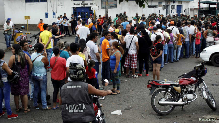 FILE - People make a line in front of Venezuelan National Guards as they wait to try to cross the border to Colombia over the Francisco de Paula Santander international bridge in Urena, Venezuela, Dec. 18, 2016.