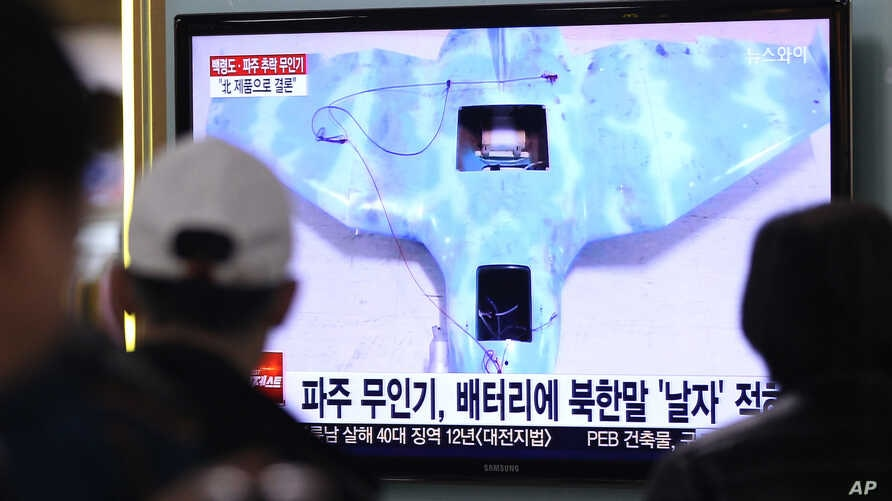 People watch a TV news program showing an unmanned drone, at the Seoul Railway Station, South Korea, April 2, 2014.