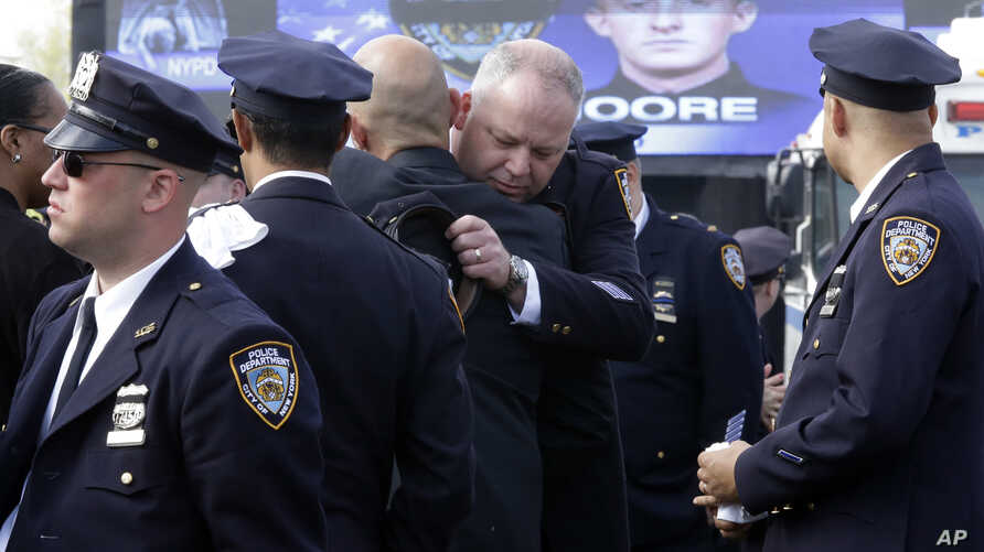 A couple of police officers embrace as they arrive for the funeral mass of New York City police officer Brian Moore, May 8, 2015, at the St. James Roman Catholic church in Seaford, N.Y.