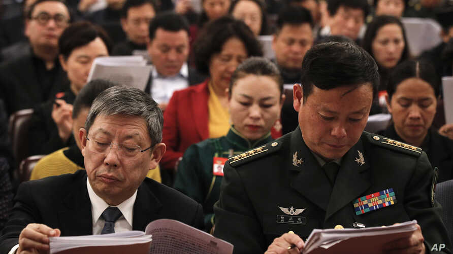 Delegates read the work reports which is delivered by Chinese Premier Li Keqiang at the opening session of the annual National People's Congress at the Great Hall of the People in Beijing, Tuesday, March 5, 2019.