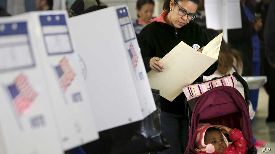 FILE - A woman looks over her ballot at a polling station in the Washington Heights section of New York, Nov. 8, 2016.