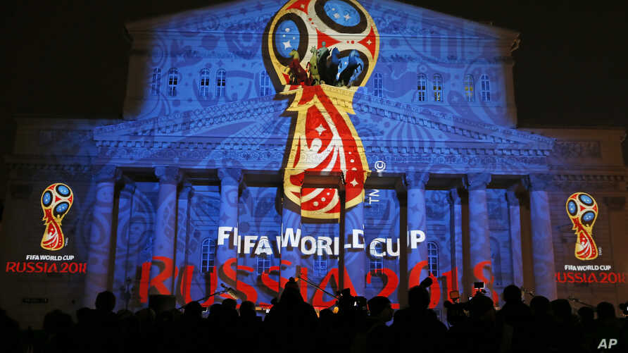 Journalists look at a light installation showing the official logotype of the 2018 FIFA World Cup during its unveiling ceremony at the Bolshoi Theater building in Moscow, October 28, 2014. REUTERS/Maxim Shemetov (RUSSIA - Tags: SPORT SOCCER WORLD CUP