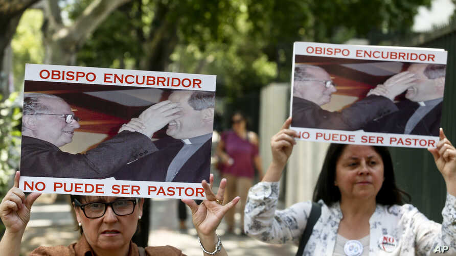 "FILE - Members of the movement Laity of Osorno hold up images showing the Rev. Fernando Karadima (L), and his protege Juan Barros, bishop of Osorno, with a message that reads in Spanish: ""A bishop who covers up cannot be a priest,"" during a protest i"