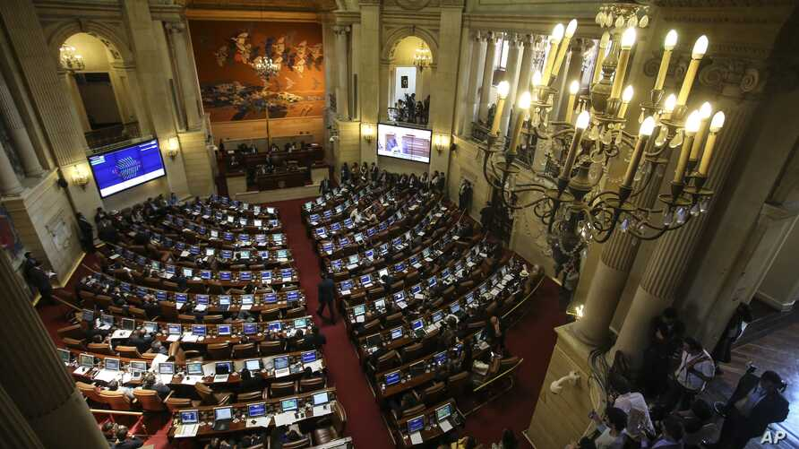 FILE - Lawmakers debate in Congress in Bogota, Colombia, Nov. 30, 2016. They have approved the creation of special courts for the prosecution of war crimes, a key component of the historic peace agreement reached with the country's largest rebel grou