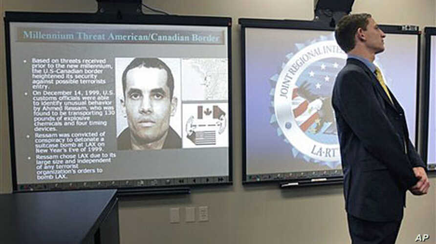 """Joel Cohen (R), with the Department of Homeland Security stands next to a giant monitor displaying Ahmed Ressam, the so-called """"Millennium Bomber,"""" at the Los Angeles Joint Regional Intelligence Center in Norwalk, California, July 2006. (file photo)"""