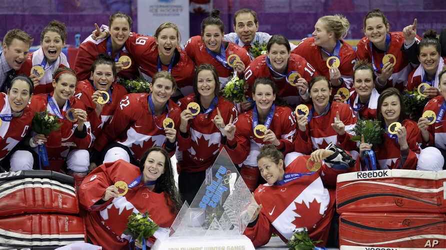 Team Canada gathers for a group photo after beating the USA 3-2 in overtime of the gold medal women's ice hockey game at the 2014 Winter Olympics, Feb. 19, 2014, in Sochi, Russia.