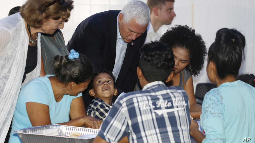 U.S. Vice President Mike Pence leans in as he visits with Venezuelan families at the Calvary Chapel in Cartagena, Colombia, Aug. 14, 2017.