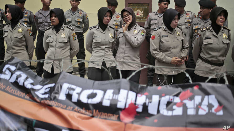 FILE -  Muslim police women stand guard during a Muslim rally against the persecution of Rohingya Muslims, outside the Embassy of Myanmar in Jakarta, Indonesia, Nov. 25, 2016.