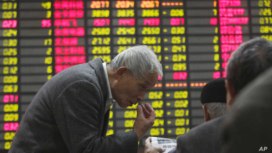 An investor gestures to another in front of the stock price monitor at a private securities company in Shanghai, China, November 22, 2012.