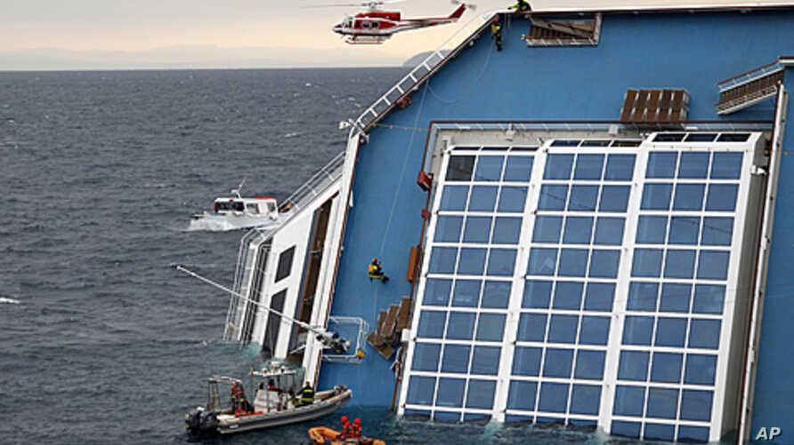 Rescue workers climb up the capsized Costa Concordia cruise ship that ran aground off the west coast of Italy at Giglio Island, January 16, 2012.