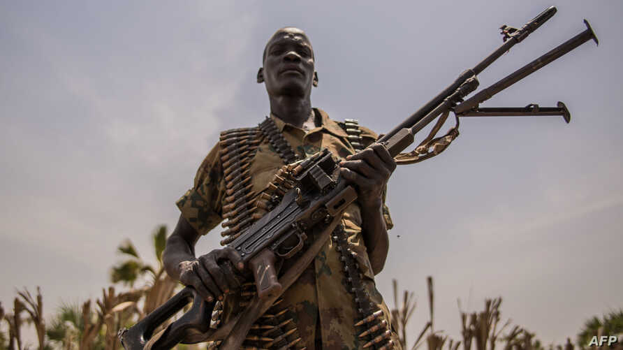 A rebel soldier poses with his gun in Touch Riak, Leer county, on March 7, 2018, where famine has been declared since February 2017.