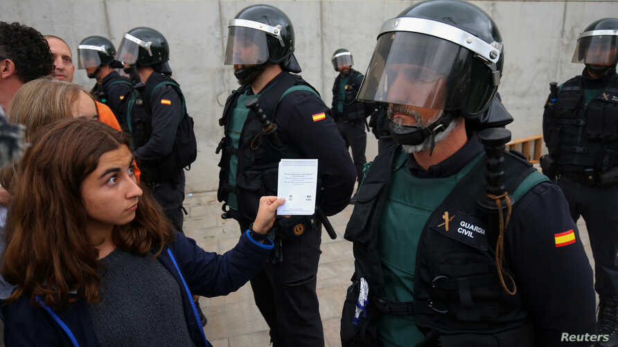 A woman shows a ballot to a Spanish Civil Guard officer outside a polling station for the banned independence referendum in Sant Julia de Ramis, Spain, Oct. 1, 2017.