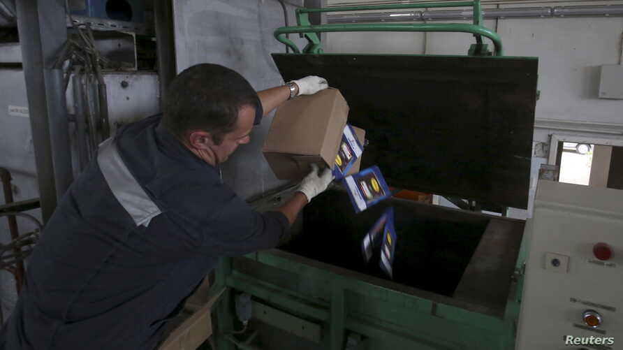 An employee throws sliced and packed meat into a furnace during the destruction of illegally imported food at a customs house at Pulkovo Airport in St. Petersburg, Russia, Aug. 6, 2015.